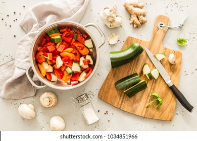 Cooking - preparing vegetable vegetarian stew (thick soup). Kitchen scenery - pot with recipe ingredients around on the grey stone worktop captured from above (top view, flat lay).