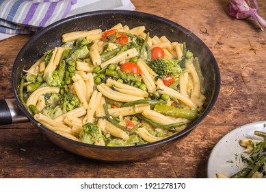 Cooking primavera pasta in a pan - vegan american and italian primavera pasta dish with broccoli, beans, asparagus, peas and tomatoes in a pan on a wooden table, top view