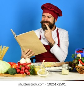 Cooking process concept. Man with beard holds recipe book or menu on blue background. Cook with happy face in burgundy uniform reads cook book having idea. Chef near pasta, vegetables and dough