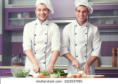 Cooking process concept. Portrait of two funny working men in cook uniform making food in modern kitchen. Indoor shot