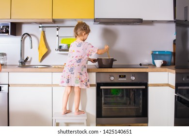 Cooking process: little cute child girl chef preparing soup while standing on the chair  to reach counter