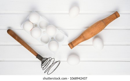 The cooking process. Plastic tray with white eggs, rolling pin, whisk on a white wooden table. Top view.