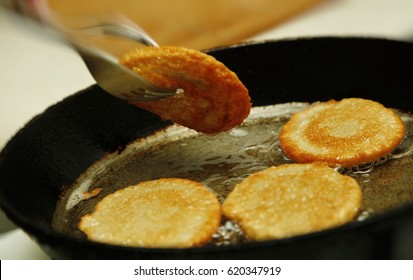 Cooking process of potato flapjacks on the pan with boiling sunflower oil close up with motion blur