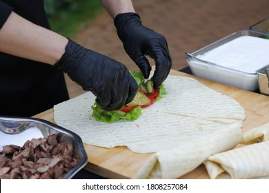 Cooking process, preparation. Lavash with meat, lettuce and tomatoes. The chef prepares in the outdoor. Shawarma with meat and vegetables. Horizontal