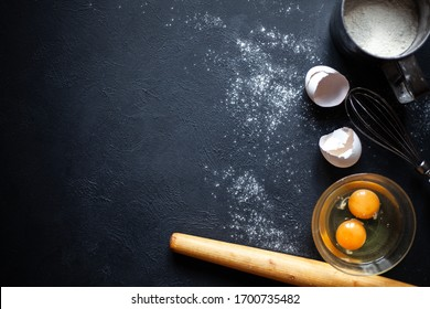 Cooking process.Flour, Eggs, Yolk, Shell, whisk,rolling pin.Flour scattered on a black concrete background.