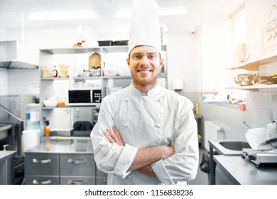 cooking, profession and people concept - happy male chef cook  in toque with crossed hands at restaurant kitchen