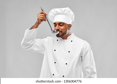 cooking, profession and people concept - happy male indian chef in toque tasting food from ladle over grey background