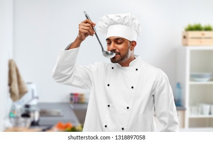 cooking, profession and people concept - happy male indian chef in toque tasting food from ladle over kitchen background