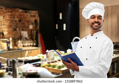 cooking, profession and people concept - happy male indian chef in toque with cookbook over restaurant kitchen background