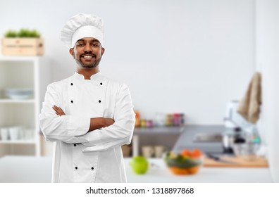 cooking, profession and people concept - happy male indian chef in toque over kitchen background