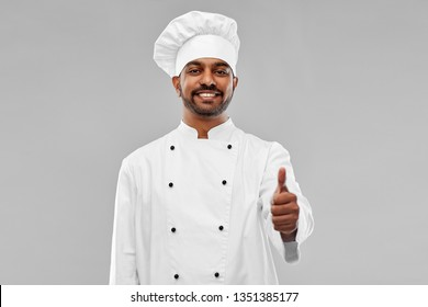 cooking, profession and people concept - happy male indian chef in toque showing thumbs up over grey background