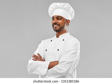 cooking, profession and people concept - happy male indian chef in toque over grey background