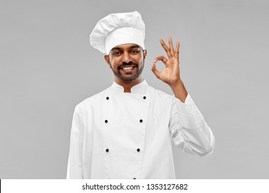 cooking, profession and people concept - happy male indian chef in toque showing ok gesture over grey background