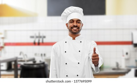 cooking, profession and people concept - happy male indian chef in toque showing thumbs up over restaurant kitchen background