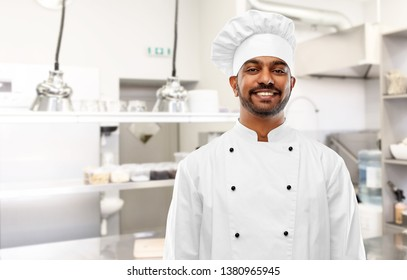 cooking, profession and people concept - happy male indian chef in toque over restaurant kitchen background