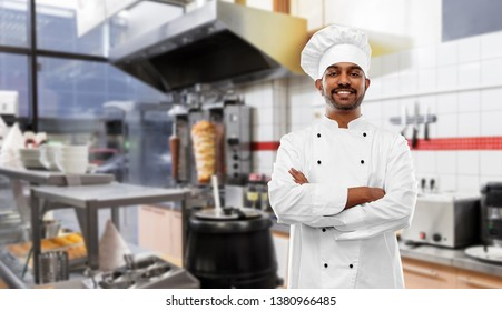 cooking, profession and people concept - happy male indian chef in toque with crossed arms over kebab shop kitchen background