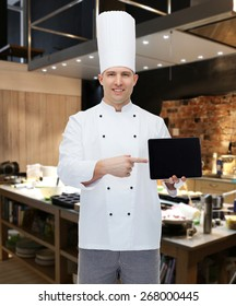 cooking, profession and people concept - happy male chef cook showing tablet pc computer black blank screen over restaurant kitchen