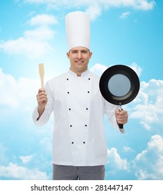 cooking, profession and people concept - happy male chef cook holding frying pan and spatula over blue sky with clouds background