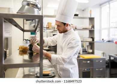 cooking, profession and people concept - male chef cook making food at restaurant kitchen