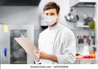 concept de cuisine, de profession et de personnes - chef masculin cuisinier avec presse-papiers portant un masque médical de protection du visage sur fond de cuisine du restaurant