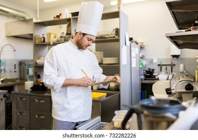 cooking, profession and people concept - male chef cook with clipboard doing inventory of restaurant kitchen fridge