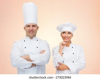 cooking, profession, teamwork and people concept - happy chefs or cooks couple over beige background