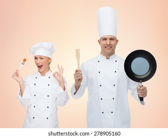cooking, profession, teamwork, and people concept - happy chefs or cooks couple with kitchenware over beige background