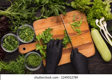Cooking at professional kitchen. Chef hands in black disposable gloves cutting parsley, top view