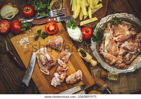 cooking raw chicken with vegetables. on a wooden background.