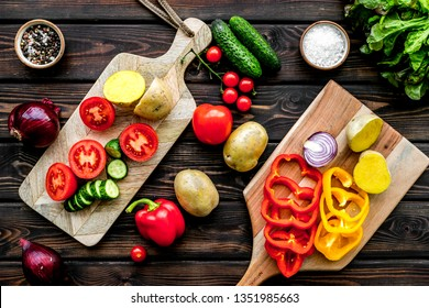cooking with raw vegetables on dark wooden background top view
