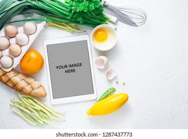 Cooking recipes on ipad with vegetables on background, copy space