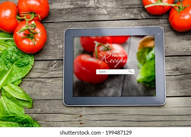 Cooking recipes on tablet pc with vegetables on background.
