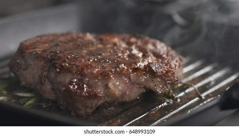 cooking rib eye steak with herbs on grill pan, wide photo