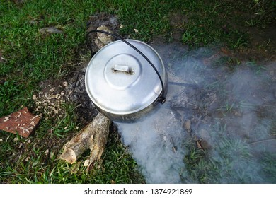 Cooking rice using cast-iron cauldron pot in outdoor nature setup. Food Camping cooking over a fire using dry firewood and use stone as stove stand.