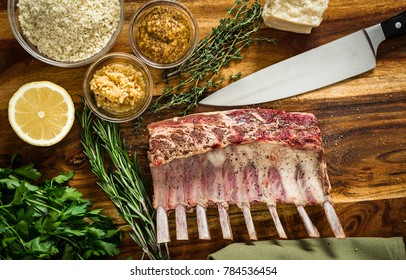 Cooking a roasted rack of lamb for dinner with a herbed parmesan cheese crust.  Ingredients rosemary, thyme, garlic, and mustard mixed with bread crumbs.  set on a cutting board with a chef knife