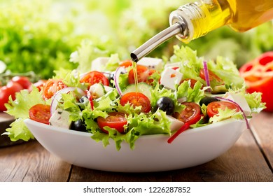 Cooking salad. olive oil pouring into bowl of fresh vegetable salad