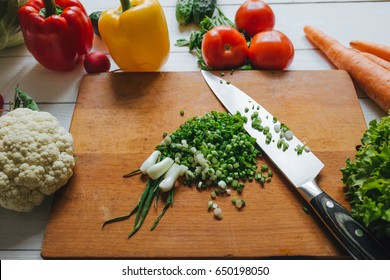 Cooking salad still. Knife and cut fresh green onion on chopping board. Vegetables border frame.