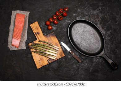 Cooking salmon with asparagus. Pan raw salmon cherry tomatos and asparagus on cutting board on black background.