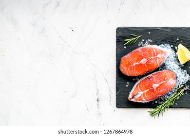Cooking salmon steak from raw fish on black plate with rosemary, lemon on marble restaurant kitchen table background top view copy space