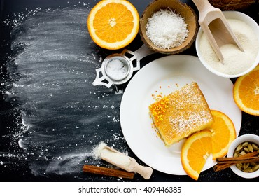 Cooking semolina pie basbousa (namoora). Slice of cake and ingredients on black background with flour top view blank space for text