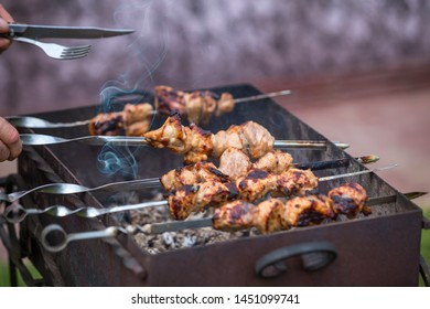 Cooking shashlik on the mangal in nature. Selective focus.