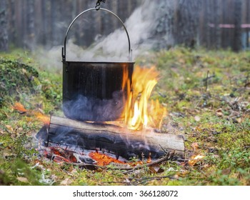 Cooking in sooty cauldron on campfire at forest. From a kettle there is steam. Close up