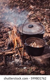 Cooking in the sooty cauldron on the open fire in woods. Cooking food at a campsite in wood