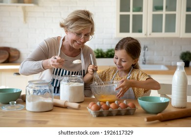 Cooking with soul. Happy little girl in apron help senior grandma at kitchen mix dough for cookies pancakes. Smiling older granny teach small grandkid to bake homemade cake pastry share family recipe - Shutterstock ID 1926117329