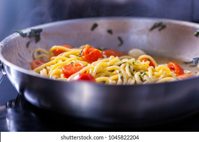 Cooking spaghetti concept. Pasta in the pan. Cooking Fresco Pasta.  Italian cuisine, tomato sauce for pasta, healthy food making, detailed view steam in the kitchen. Flipping pasta in the air