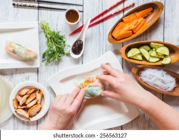 Cooking spring roll, top view, hands - mooving blur