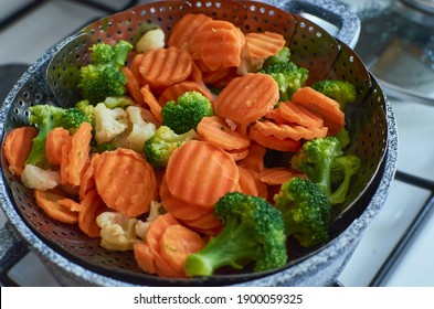 Cooking of steamed sliced vegetables veggies broccoli, cauliflower, carrot medley, mix in steamer basket pot. Healthy eating, lifestyle, bright and colorful food photo.