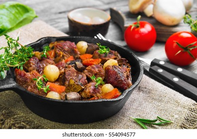 Cooking Stew meat in Burgundy (Beef Bourguignon) in cast iron frying pan with carrots, onions. Spices for Beef Bourguignon thyme, cherry tomatoes, mushrooms champignons. Gray wooden background.