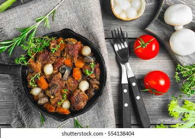 Cooking Stew meat in Burgundy (Beef Bourguignon) in cast iron frying pan with carrots, onions. Spices for Beef Bourguignon thyme, cherry tomatoes, mushrooms champignons Wooden table Top view, flat lay