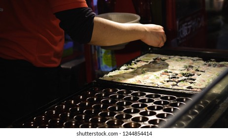 Cooking street food of Octopus meat balls called Takoyaki on hot pan. Takoyaki is a most famous Japanese snack food in Japan.